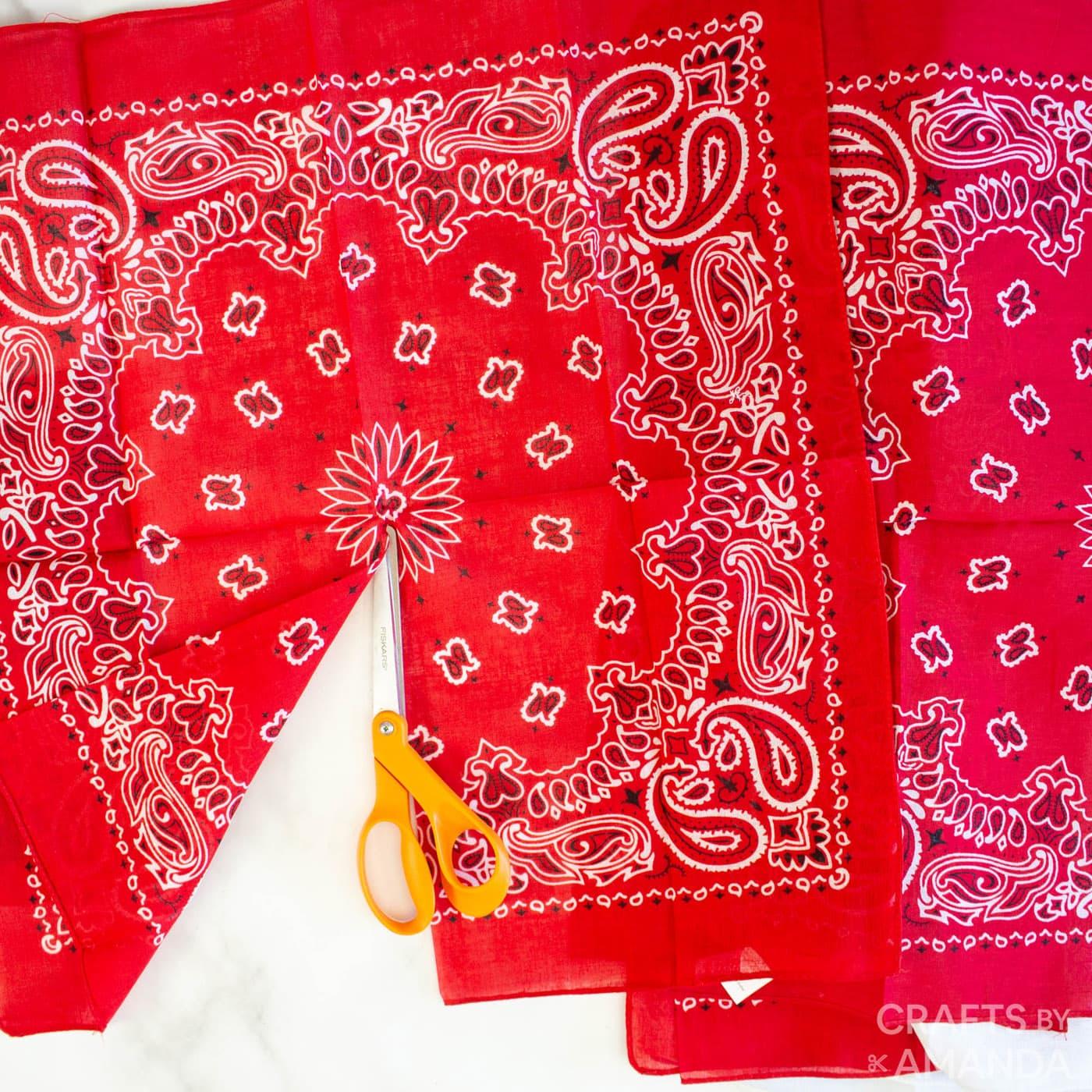 scissors cutting red bandana in half