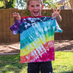 boy holding up shirt he tie dyed