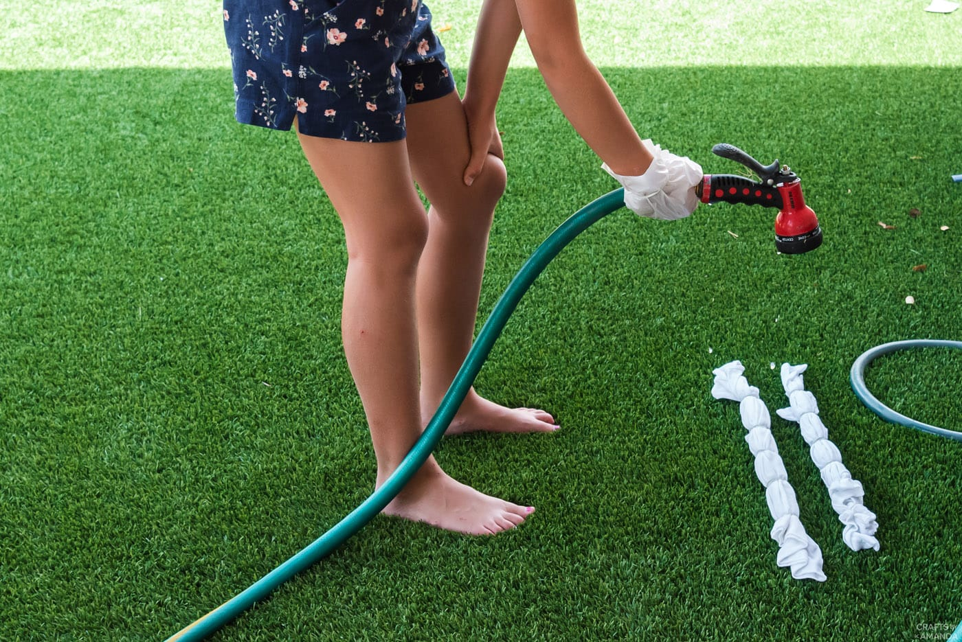 girl using a hose to wet a shirt