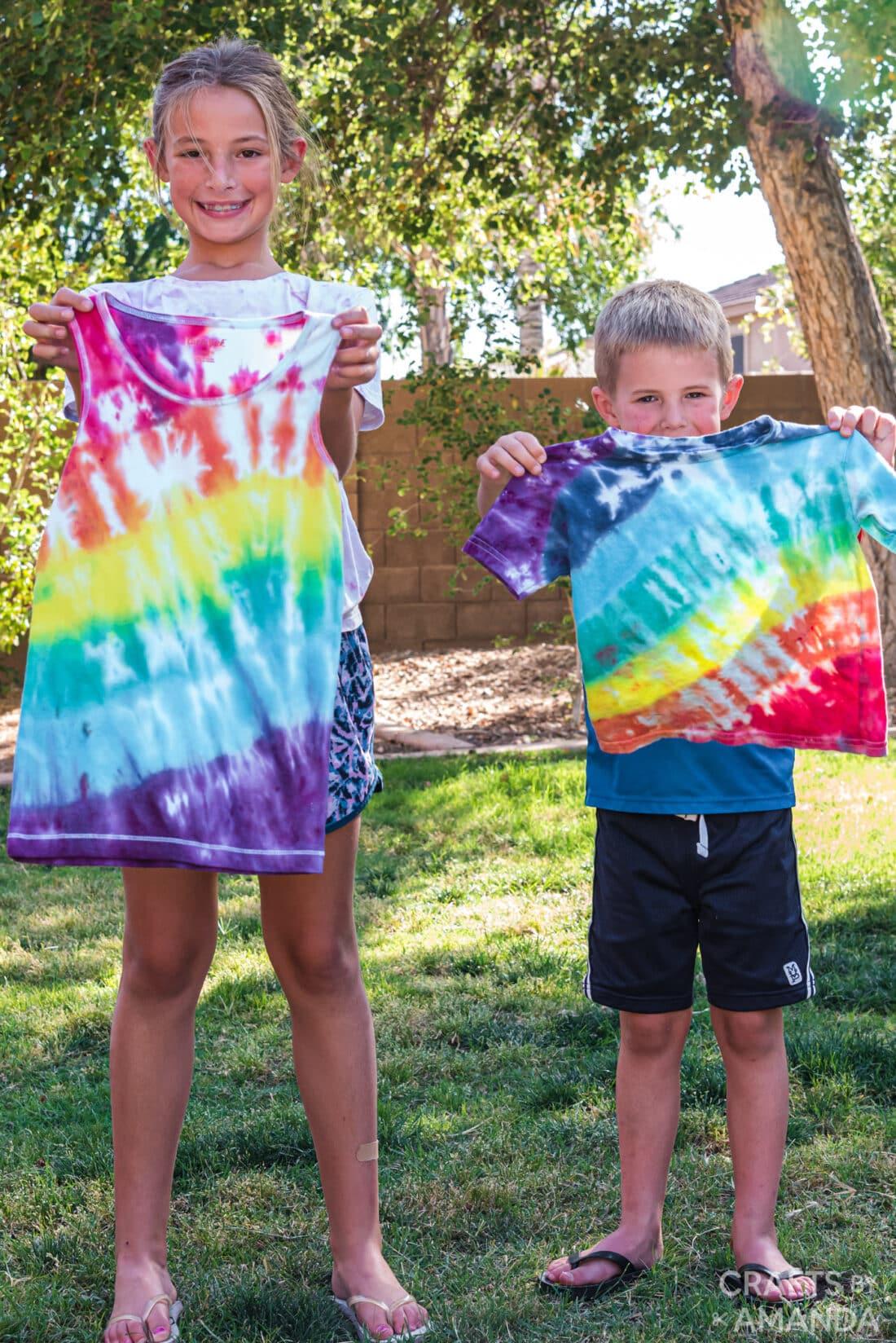 kids holding up rainbow tie dye shirts