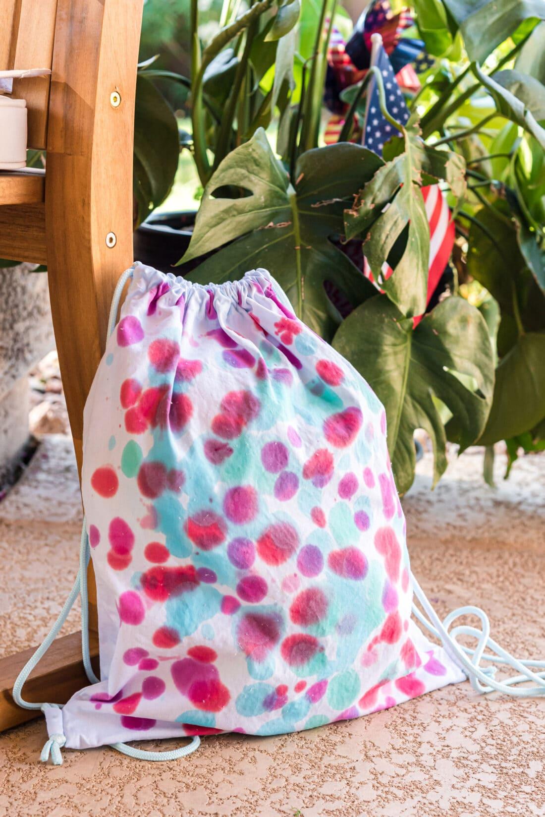 Drip Tie Dye Backpack sitting on the floor