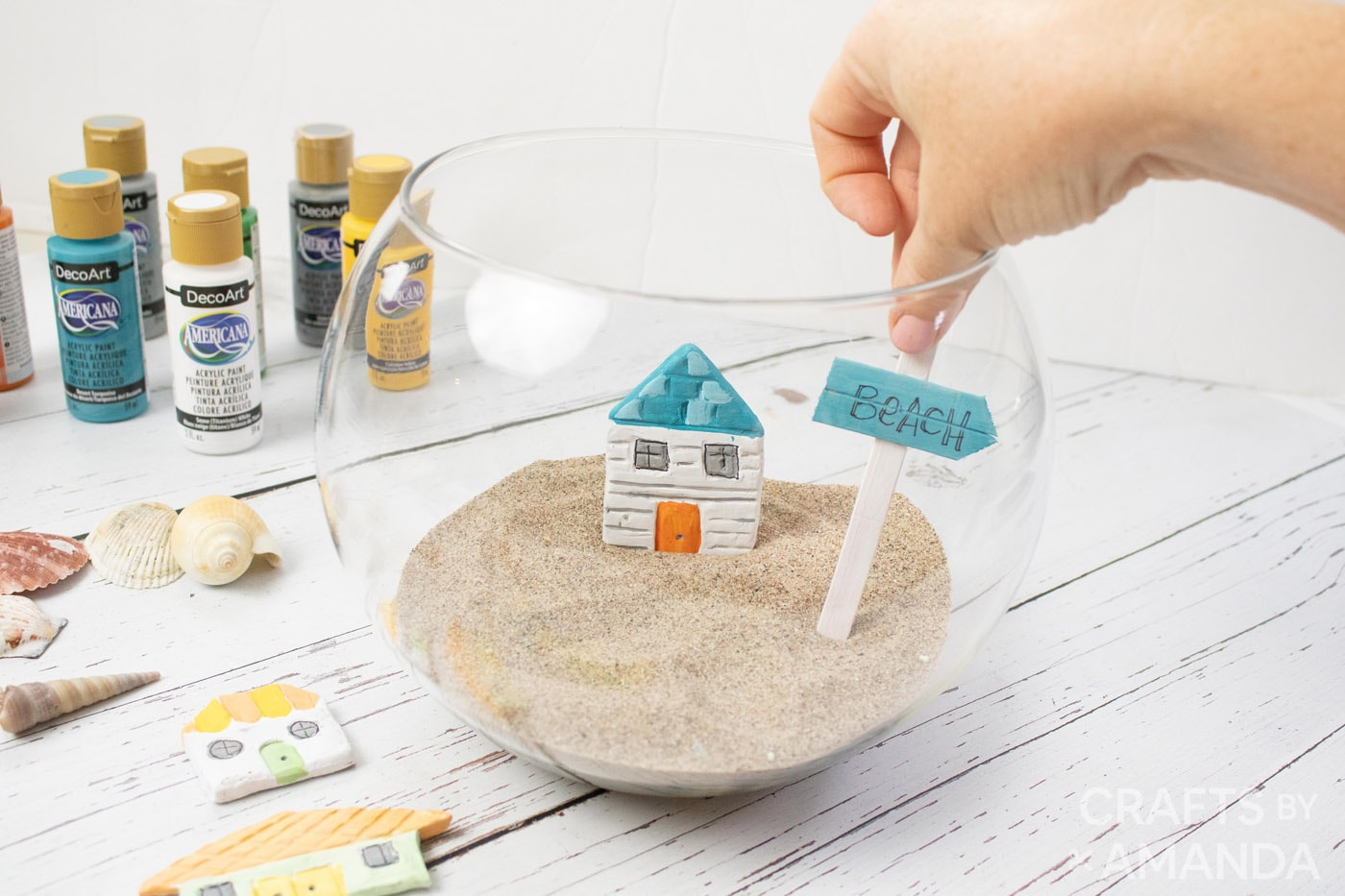 placing clay house and popsicle stick sign into fishbowl with sand