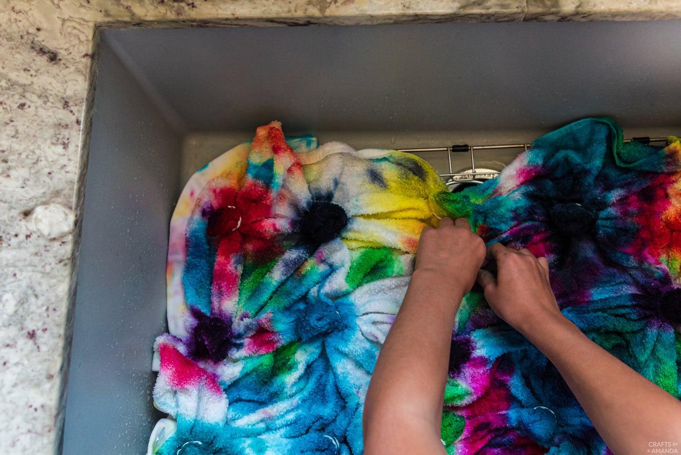 rinsing tie dye beach towels in the sink