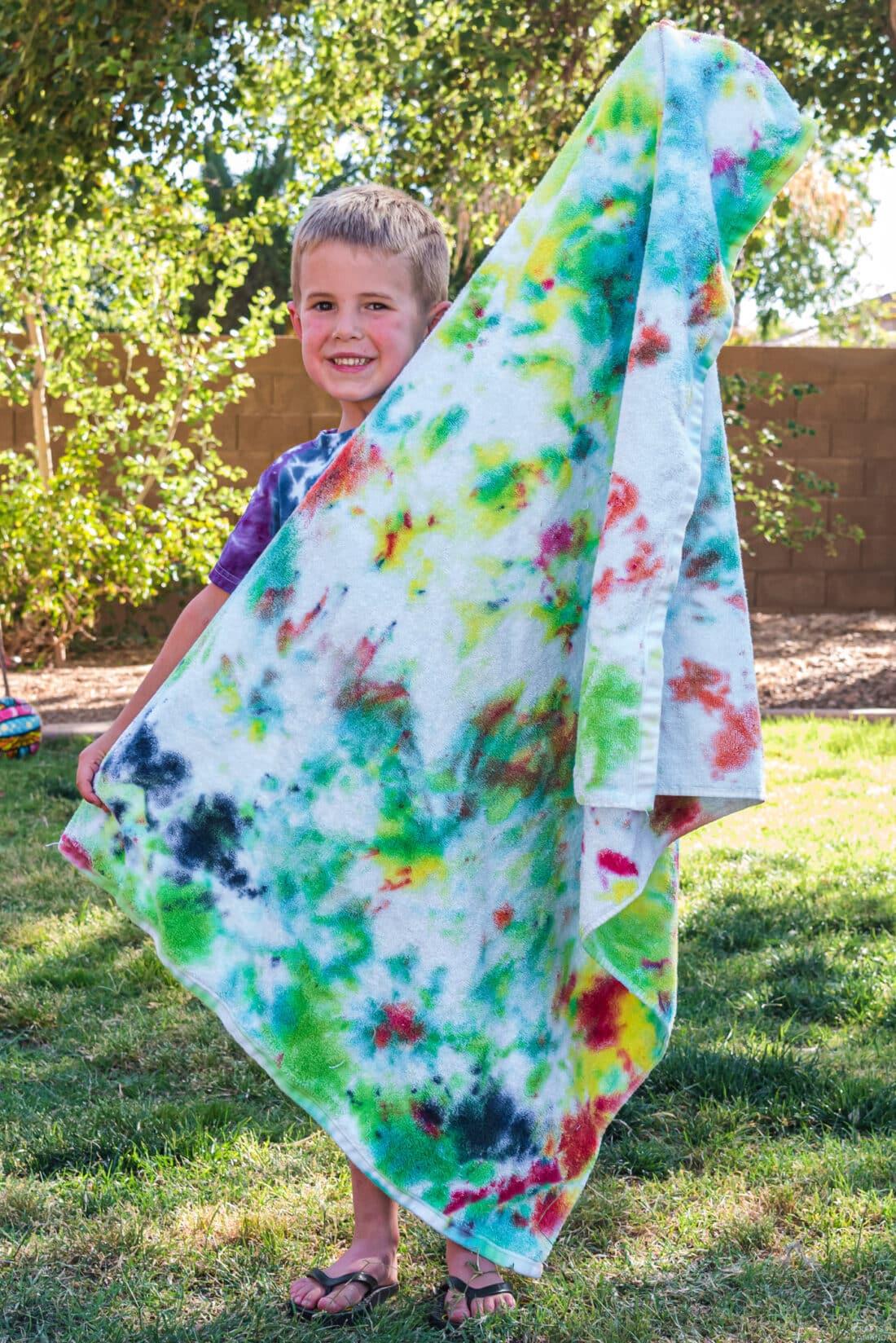 boy holding Tie Dye Beach Towel