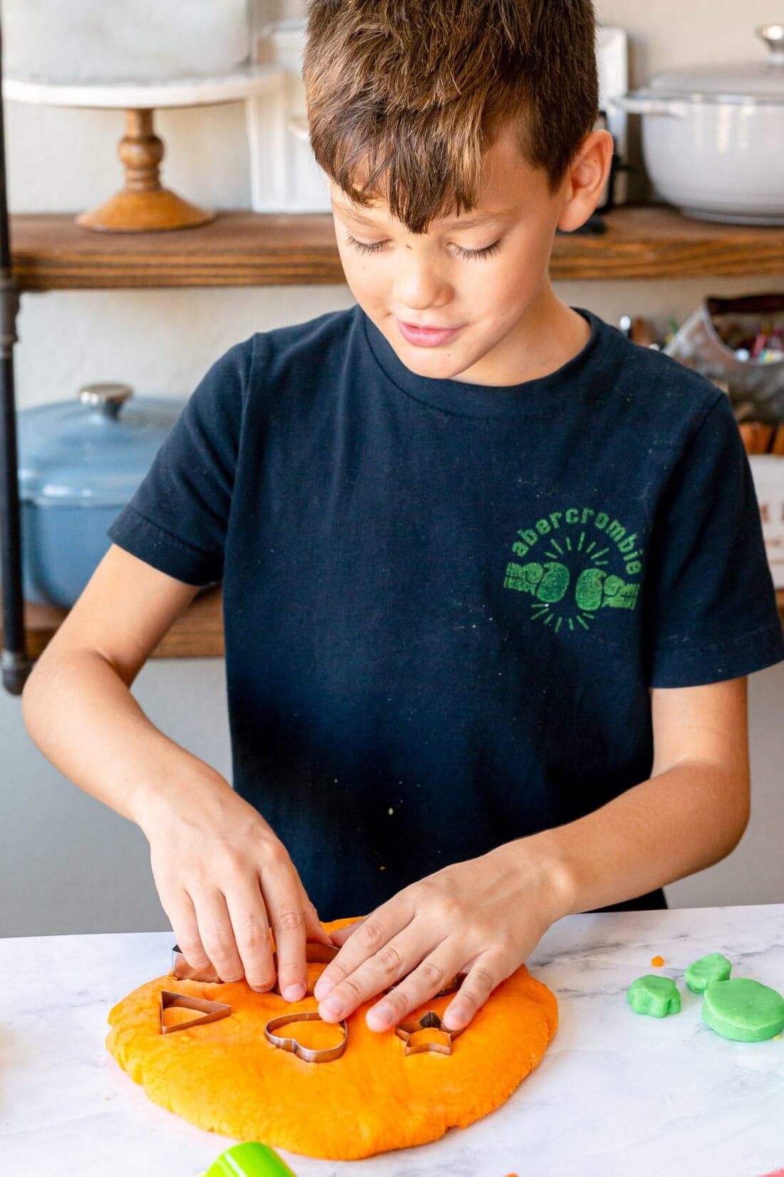 jongen die koekjesvormpjes gebruikt op deeg