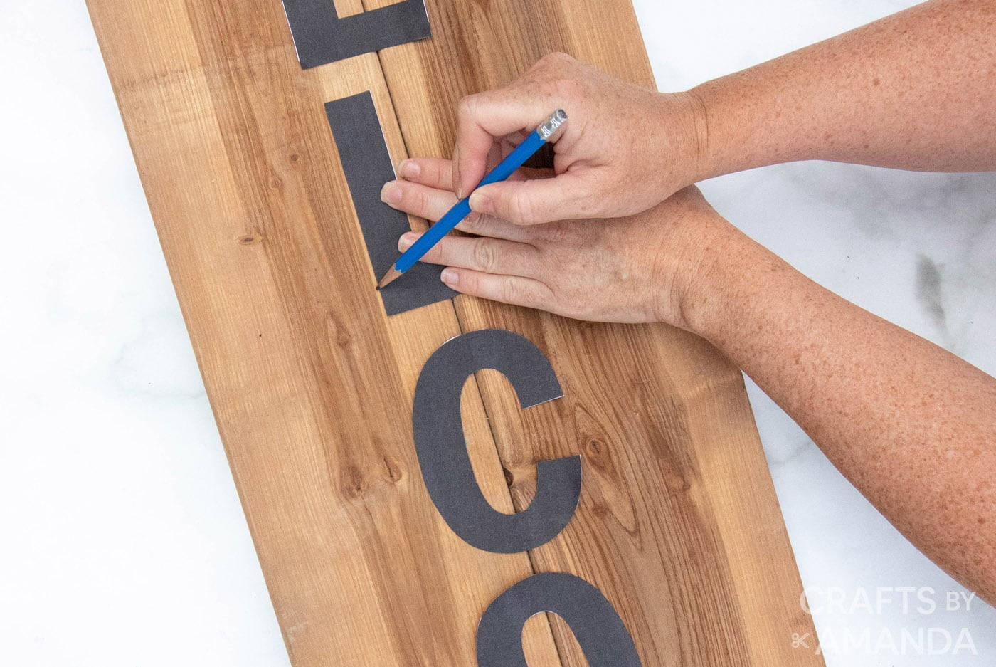 hand tracing letters onto wooden board