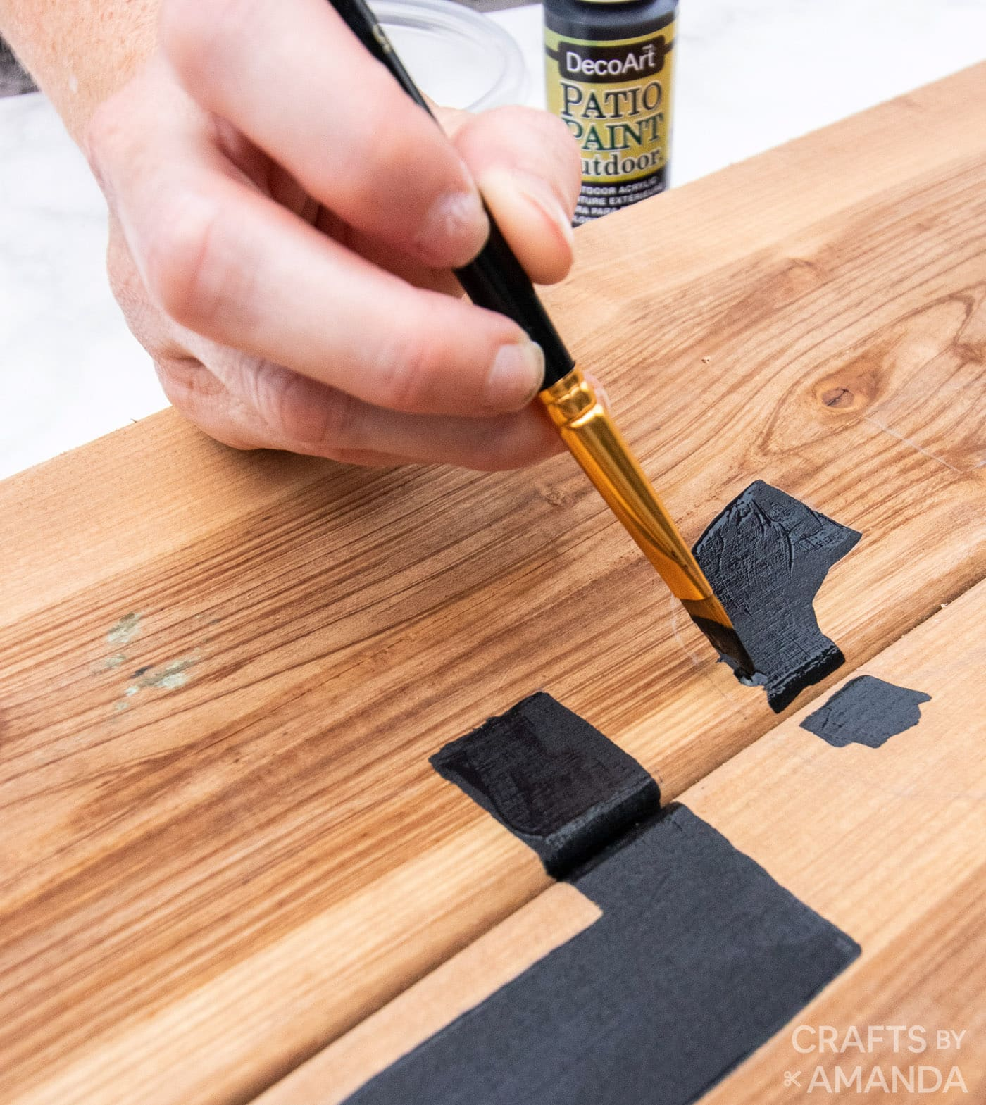 hand painting letter onto wooden board