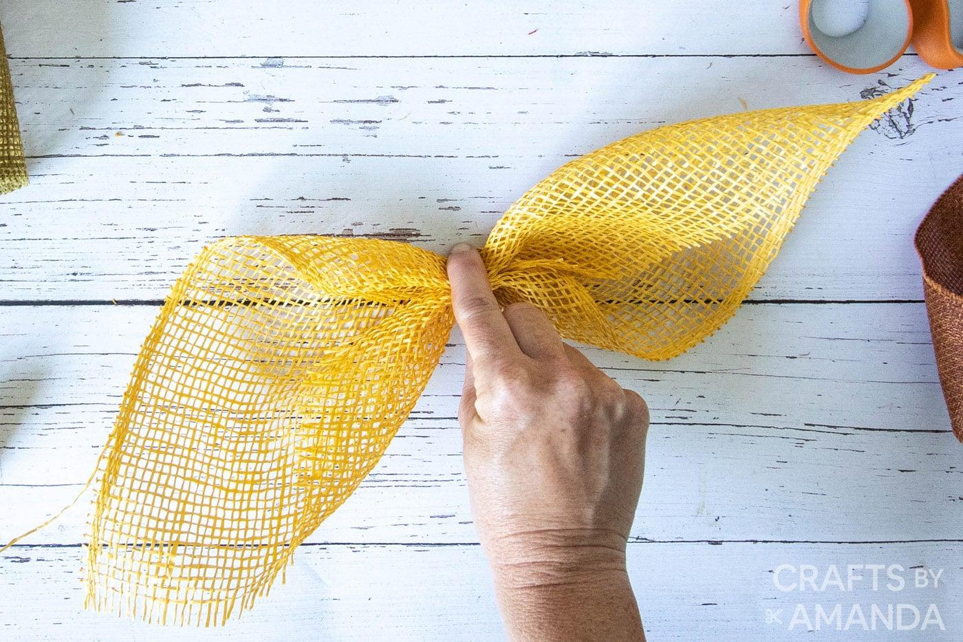 cinching gele jute om een zonnebloembloemblaadje te vormen