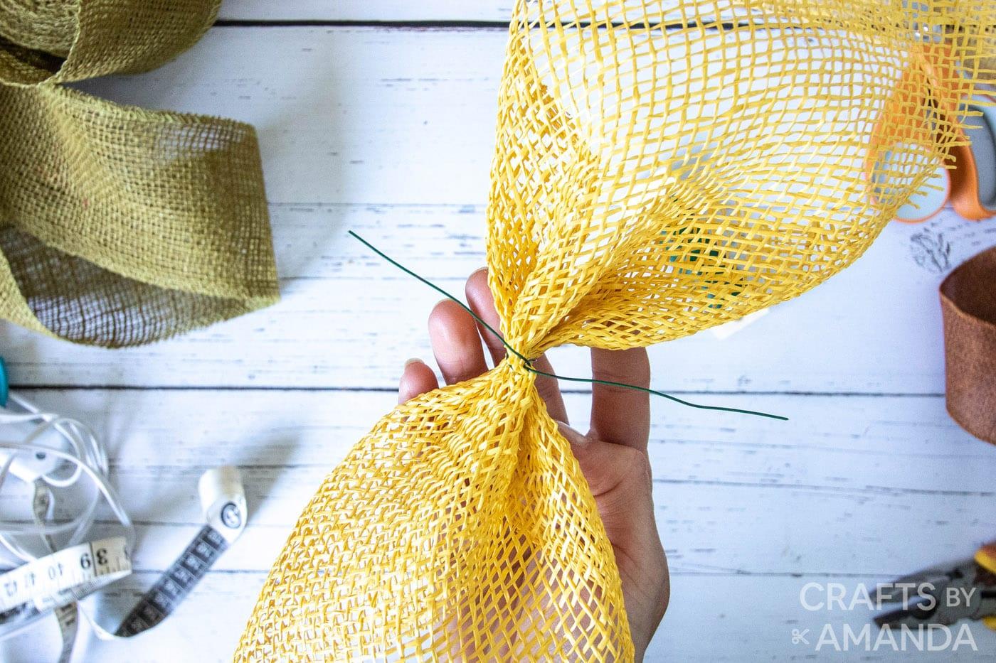 vastzetten van gele jute cinch met bloemendraad