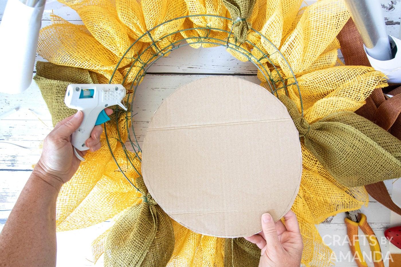 hand met cirkel kartonnen uitsnede opnieuw zonnebloem krans