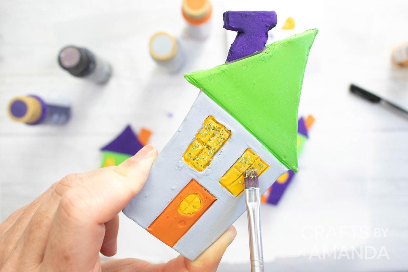 met de hand schilderen van gele ramen op huis